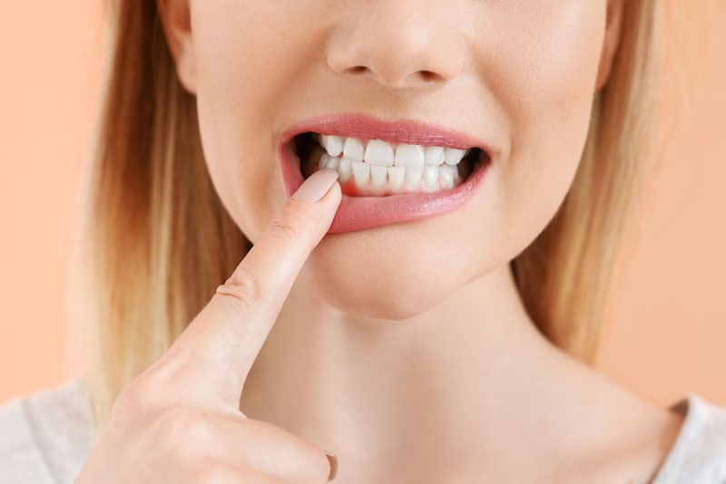 A featured website image for an emergency dentist belleville featuring a woman pointing at her teeth