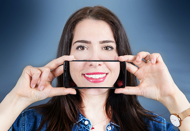 A featured website image for a trenton dentist of a woman with smartphone that takes a picture of her smile