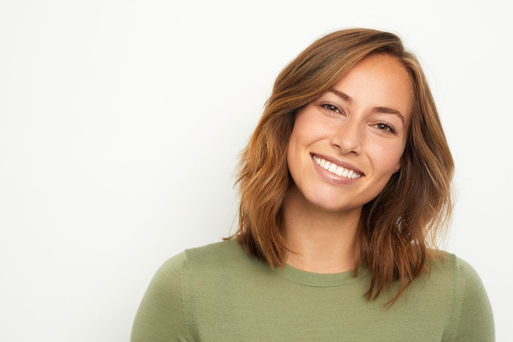 A featured website image for trenton teeth whitening featuring a woman with whitened teeth smiling